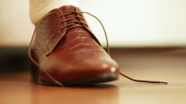 Man tying shoelaces on expensive brown shoes — Stock Video