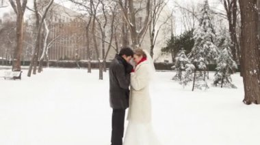 Newlyweds heat each other in the snow in a winter park — Stock Video