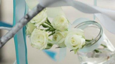 Appeso in un vaso con rose bianche di acqua. componenti decorazioni di nozze. — Video Stock