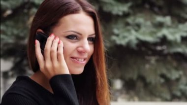 Beautiful girl looks up and starts talking on mobile phone, smiling while doing so. — Stock Video