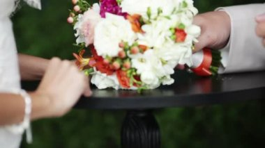 Groom gives the wedding bouquet and takes a bride's hand — Stockvideo