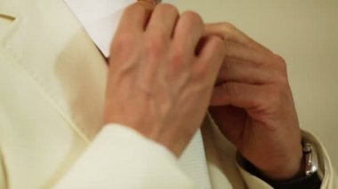 Groom tightens tie. Groomsman helps him and corrects scarf — Stock Video
