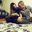 Young couple considering children's photos for adoption — Видео