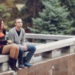Brother and sister sitting on the parapet and acting up — Stock Video