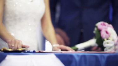 Newlyweds by turns sign a marriage contract. — Stock Video
