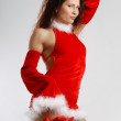 Female Santa in sexual red dress on light background — Stok fotoğraf