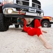 Sexy woman repairing the red jeep — Stok fotoğraf