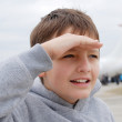 Royalty-Free Stock Photo: Boy peering with palm near brow against airplane, focus on the f
