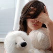 Stock Photo: Teenage girl with teddy bear, face hidden with hand