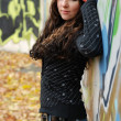 Teenage dreamy girl near graffiti wall — Stockfoto