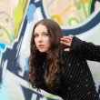 Teenage girl listens against graffiti wall — Stock Photo