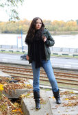 Teenage girl in wind-breaker and jeans against river — Stock Photo