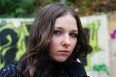Portrait of teenage girl against the wall graffiti blurred — Stock Photo