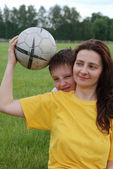 Woman holds football, boy peeps out from behind her — Stock Photo