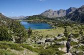 Hiker descending to the mountainous lake — Stock Photo