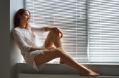 A woman on the windowsill at home — Stock Photo