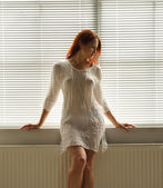 A woman by the window at home — Stock Photo