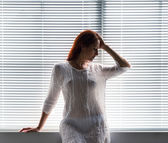 A woman near the window at home — Stock Photo