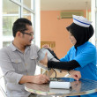 Stock Photo: Confident Muslim patient checking blood pressure by nurse