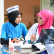 Confident Muslim doctor and nurse in head scarf at hospital — Stock Photo #31377321