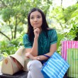 Beautiful shopping woman happy holding shopping bags take rest at garden and smile — Stock Photo #31378297