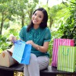 Beautiful shopping woman happy holding shopping bags take rest at garden and smile — Stock Photo #31378299