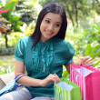 Beautiful shopping woman happy holding shopping bags take rest at garden and smile — Stock Photo #31378313