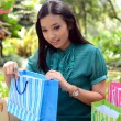 Beautiful shopping woman happy holding shopping bags take rest at garden and smile — Stock Photo
