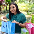 Beautiful shopping woman happy holding shopping bags take rest at garden and smile — Stock Photo #31378345