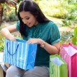 Beautiful shopping woman happy holding shopping bags take rest at garden and smile — Stock Photo #31378347