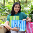 Beautiful shopping woman happy holding shopping bags take rest at garden and smile — Stock Photo #31378377