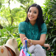 Beautiful shopping woman happy holding shopping bags take rest at garden and smile — Stock Photo #31378389
