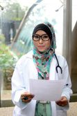 Young asian muslim woman doctor in head scarf smile while holding medical report — Stock Photo