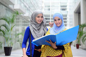 Two young pretty Asian muslim business woman in head scarf — Stock Photo