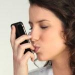 Brunette kissing mobile telephone — Stock Photo
