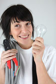 Female electrician holding replacement wiring and bulb — Stock Photo