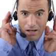 Call centre operator looking shocked - Stock Photo