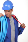 Young worker with blue flexible tube and a wrench — Stock Photo