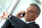 Businessman looking at his watch whilst on the phone — Stock Photo