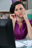 Wistful woman at a desk — Stock Photo