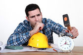 Tired tradesman about to smash his alarm clock — Stock Photo