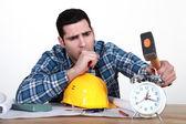 Tired tradesman about to smash his alarm clock — Stock Photo
