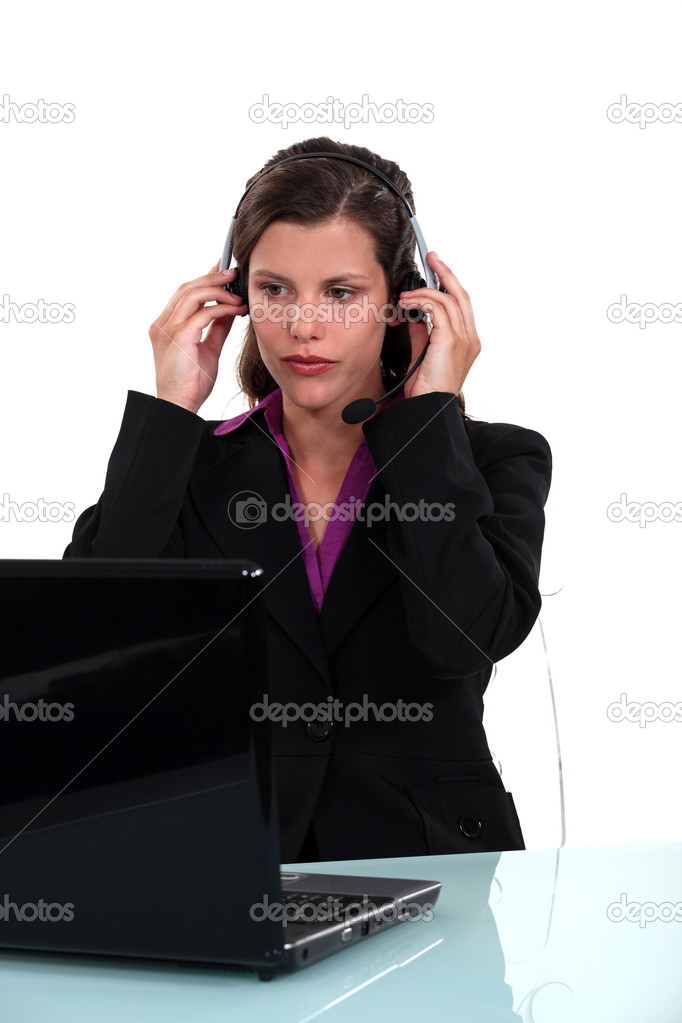 Businesswoman putting on her headset and working on her laptop — Stock Photo #13759201