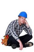 Bored builder sat on the floor — Stock Photo