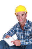 Portrait of a worker writing in notebook — Stock Photo
