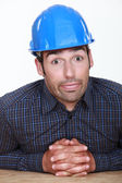 Workman sitting at table with joined hands making grimace — Stock Photo