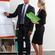 Business executives standing at a white board — ストック写真