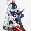 Stockfoto: Electriciperched on step ladder