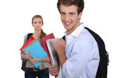 Self-confident student and sad girl in background — Stock Photo