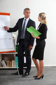 Business executives standing at a white board — Stock Photo